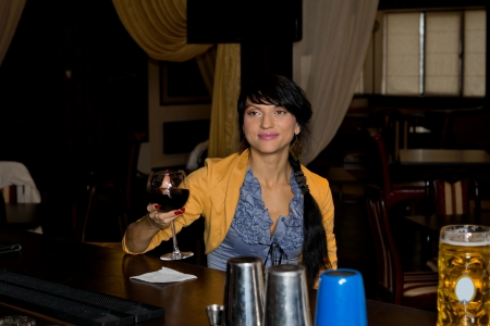 inebriated: Smiling woman making a toast raising her glass of red wine as she sits alone at the counter in a pub or bar, with copyspace Stock Photo