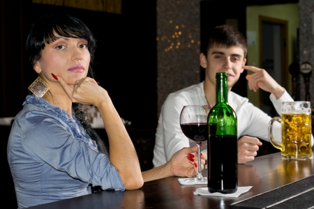mellow: Sophisticated young woman drinking at a bar enjoying a bottle of red wine turning to look at the camera with a man in the background
