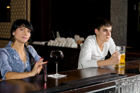 Two strangers drinking at a bar with a pretty stylish woman and attractive young man ignoring each other as they drink alone