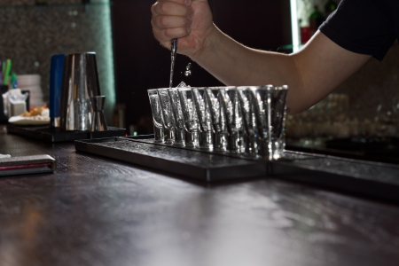 angle bar: Close-up of the hand of the barman pouring liquor into shot glasses aligned on the bar, shot from low angle Stock Photo