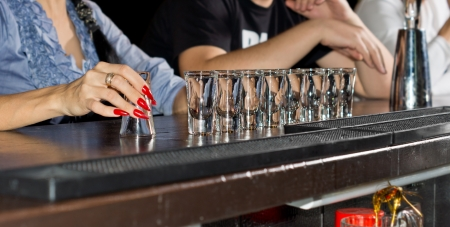 tots: Hand of an elegant woman with beautifully manicured red nails holding an empty shot glass with a row of full glasses alongside lined up on the bar counter