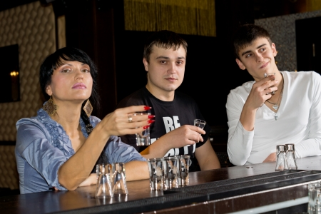 evening out: Three young friends enjoying an evening out together downing shots of vodka as they sit at a counter in a pub or nightclub