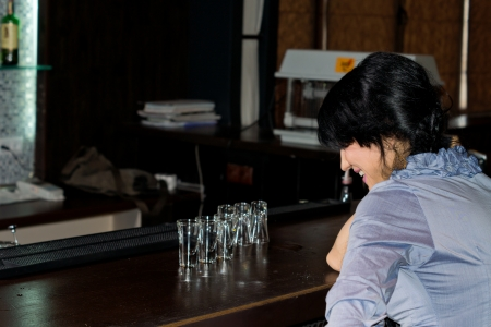 inebriated: Inebriated woman with empty vodka glasses in front of her sitting at the bar counter laughing and giggling