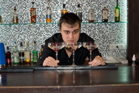 bending down: Bartender preparar tres vasos de c�ctel de alcohol para servir a los clientes de flexi�n hacia abajo para comprobar los niveles de l�quido