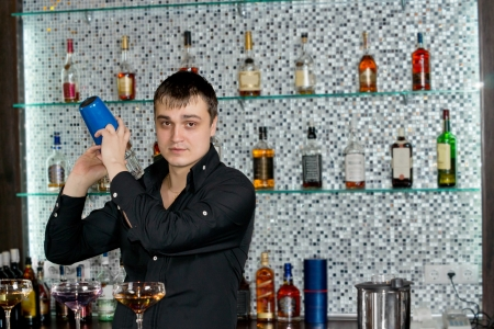 alcohol bottles: Young professional Caucasian bartender mixing liquors with the cocktail shaker at the bar, in a stylish club with bottles of alcoholic beverages aligned on shelves on the wall