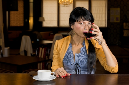 Attractive young woman drinking wine and coffee at a bar counter sipping from a large wineglass while glancing across at the camera photo