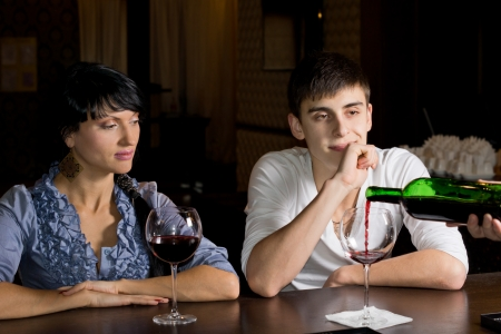 refills: Bartender pouring wine watched by a young couple seated at the counter as he refills the mans glass from a bottle