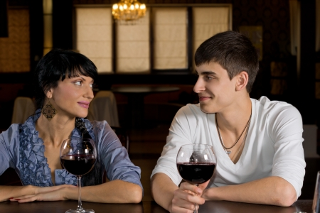 Smiling young couple on a date out drinking and celebrating with large glasses of red wine as they sit smiling into each others eyes photo