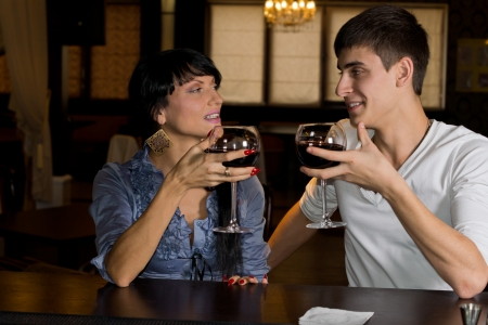 Young couple drinking red wine at a bar counter smiling and chatting as they look at each other and celebrate their friendship photo