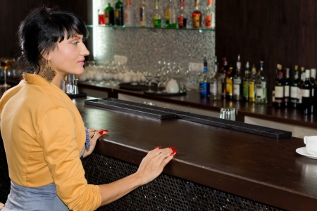 Young woman waiting for service at the bar counter sitting with her hands resting on the wood as she watches the barman who is off frame