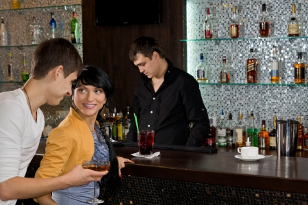 Young man chatting up a woman at the bar approaching her from behind with a drink in his hand as they both enjoy happy hour at the pub