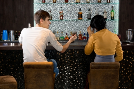 View from behind of a young couple sitting drinking at the bar in a nightclub with a display of alcoholic beverages behind them