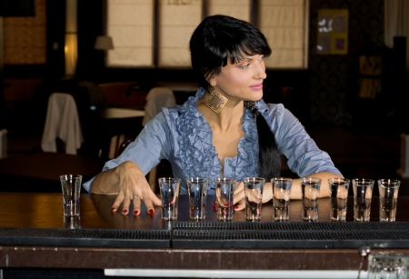 aligning: Woman with a row of vodka shot glasses lined up in front of her sitting at a bar counter smiling and looking away to the side