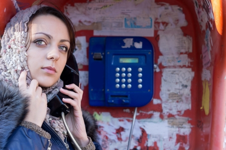 payphone: Closeup of the face of an attractive woman in a headscarf making a public telephone call from a phone booth standing with the receiver to her ear