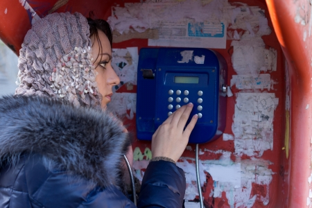 make public: Beautiful young woman standing dialling a number to make a connection on a public telephone in a booth alongside an urban street
