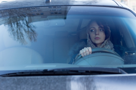 View through the windscreen of a careful female driver checking for traffic in her rear view mirror and maintaining an awareness of her surroundings