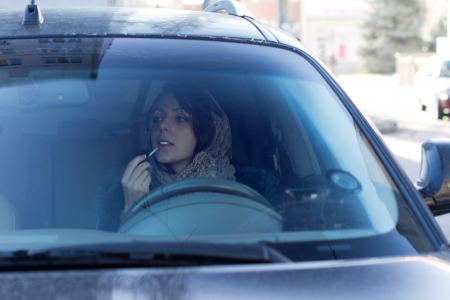 endangering: Dangerous irresponsible female driver applying her makeup using the rear-view mirror as she drives to work endangering herself and other motorists by her inattention