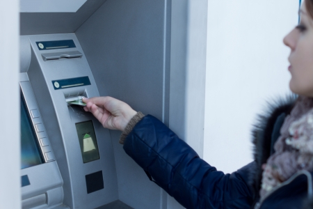automatic teller machine: Woman inserting her bank card in an ATM as she prepares to with draw or deposit money