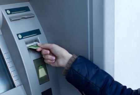 Mujer de insertar su tarjeta bancaria en un cajero autom�tico frente a un banco para que pueda retirar dinero en efectivo mediante la introducci�n de su c�digo PIN