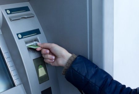 pin code: Woman inserting her bank card at the ATM outside a bank so that she can withdraw cash by entering her pin code