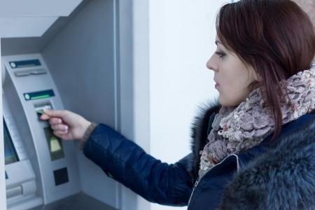 automatic transaction machine: Mujer de recuperar su tarjeta de cr�dito en el cajero autom�tico a la espera de que se dispense de la ranura despu�s de que ella ha hecho un retiro de efectivo