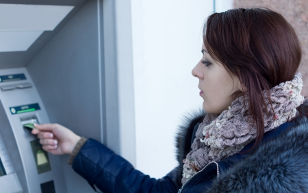 Woman using an Automated Teller machine at a bank inserting her bankcard into the slot of the machine to start her withdrawal transaction Фото со стока