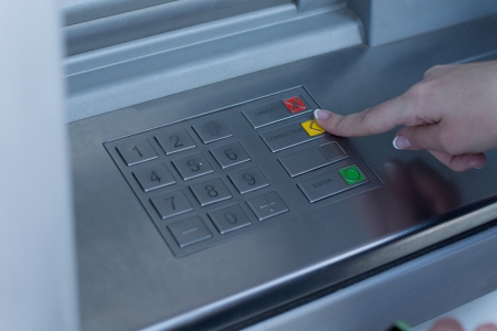 enabling: Woman selecting a transaction on a bank ATM depressing the yellow button with her finger enabling her to withdraw cash from the automated teller