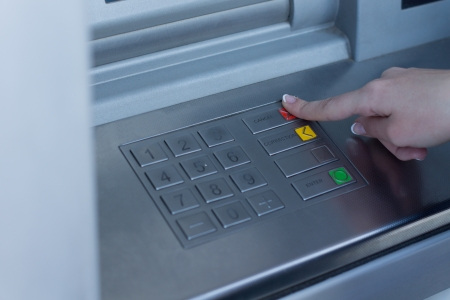 pin code: Woman selecting a transaction type on the bank ATM depressing the red button with her finger as she completes the validation of her identification and pin code