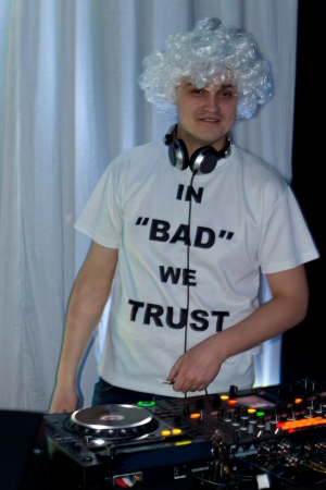 catchy: Fun attractive male DJ in a curly white wig and catchy t-shirt standing at his deck at a party mixing music and pausing to smile at the camera Stock Photo