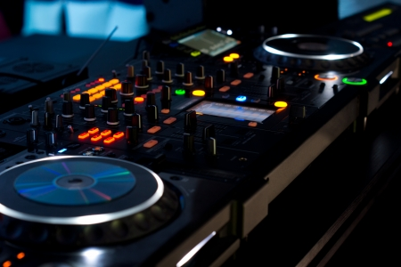 switches: Music deck at a disco with two turntables and multiple switches and sliders illuminated with colourful lights at night in a discotheque Stock Photo