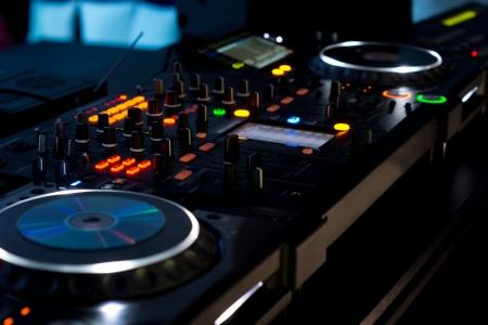 the switch: Ponte musica in una discoteca con due giradischi e molteplici interruttori e cursori illuminati con luci colorate di notte in una discoteca Archivio Fotografico