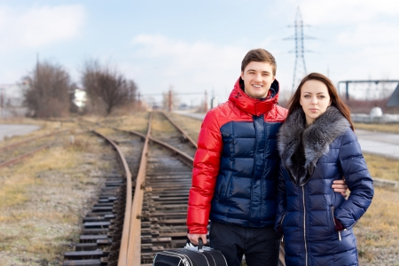 commence: Young couple waiting on the railway tracks with a suitcase standing arm in arm as they await the arrival of the train to commence their vacation