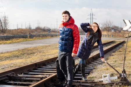 fiddles: Playful couple waiting for a train with luggage standing alongside the track near a rural level crossing with the girl saluting as she fiddles with a lever