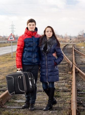 commence: Young couple standing arm in arm in the middle of a rural railway track with their luggage waiting for the train to arrive to commence their journey Stock Photo