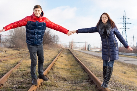 Attractive trendy young couple having fun balancing on a railway line holding hands in an attempt to stabilise each other and keep their balance