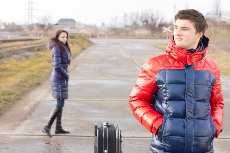 emigranti: Bel giovane in attesa in mezzo alla strada con una valigia pazientemente in piedi con le mani in tasca, mentre una donna yong cammina da dietro di lui