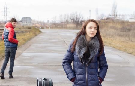 emigranti: Bella giovane donna in attesa di un passaggio in piedi con le mani in tasca su una strada di campagna con una valigia come un giovane uomo a piedi a turno per darle uno sguardo riconoscente