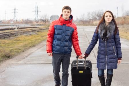 emigranti: Giovane uomo e la donna tirando lungo una valigia mentre camminano insieme lungo una strada di campagna lungo una linea ferroviaria