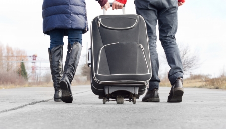 Low angle view of a couple pulling a suitcase walking side by side along an asphalt road in the countryside, closeup view of their feet and the case
