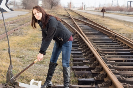 split rail: Young woman changing the points on a railway track to change the direction of travel into a siding pulling at the lever as she watches to make sure the train is not in sight