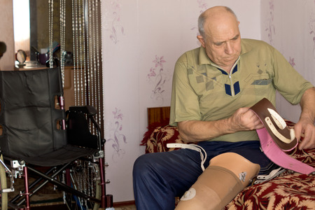 amputation: Senior man sitting on his bed fitting a prosthetic leg following an above the knee amputation sorting out the attachment straps