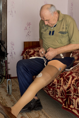 attaching: Senior man sitting on the edge of his bed at home attaching a prosthetic limb to his leg following an amputation due to injury or illness