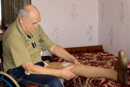 attaching: Elderly amputee fitting his artificial leg sitting in his wheelchair attaching electronic sensors to the prosthetic