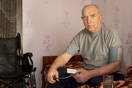 amputation: Senior man moniotoring his blood pressure using a pressure cuff and sphygmomanometer sitting on his bead at home