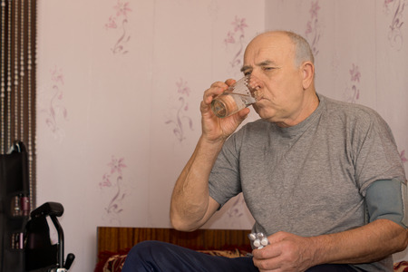 Elderly man taking his medication drinking the tablets down with a glass of water Stock Photo