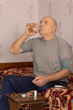 swallowing: Senior man swallowing down his medication as he sits at a small table with an assortment of tablets and pills Stock Photo