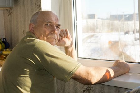 looking behind: Lonely senior man sitting at a window turning to look at the camera with a serious thoughtful expression