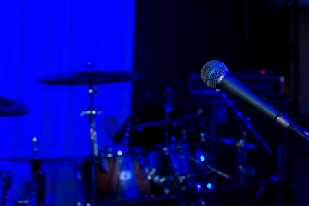 Rock or jazz concert background with a microphone set up in front of the equipment and instruments of a band on stage ready for a live concert performance in colourful blue lighting photo