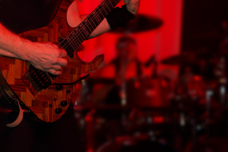 Male guitarist in a rock band performing live on stage at a festival or concert or in a nightclub in atmospheric red lighting, close up of the guitar and his hands photo