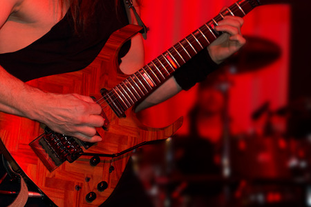 Lead guitarist playing electric guitar in a rock or jazz band during a live performance under red spotlights, close up view of his hands strumming the strings of the guitar photo